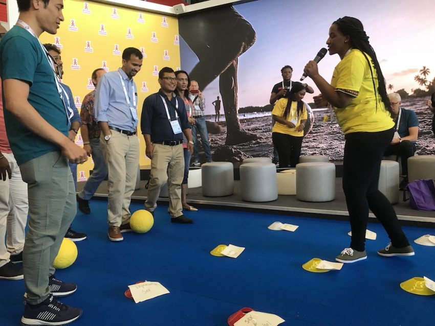 "AIDS 2018 delegates participate in ""Risk Field"", a GRS SKILLZ activity, at the MenStar booth in the Global Village."